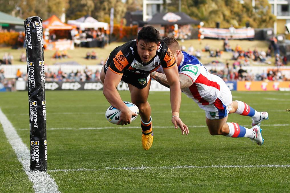David Nofoaluma of the Tigers dives over to score the opening try during the round 23 NRL match between the Wests Tigers and the Newcastle Knights at Campbelltown Sports Stadium.  Photo by Brendon Thorne/Getty Images