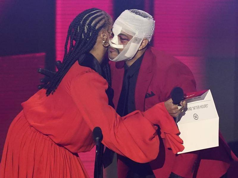 The Weeknd gave no reason for his heavily bandaged appearance at the American Music Awards.